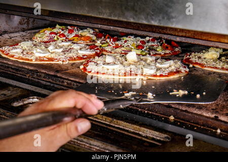 Chef putting pizza ready for baking in the electric oven - Stock Photo