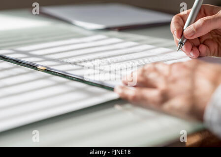 Closeup low angle view of man signing a contract or document with light from the window falling on the paperwork. - Stock Photo