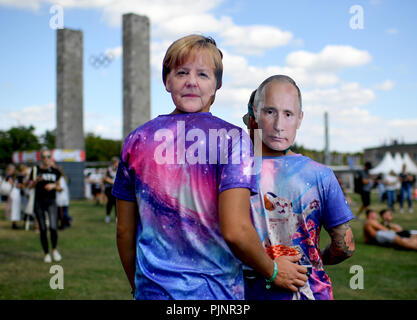 Berlin, Germany. 08th Sep, 2018. Visitors with masks by Merkel and Putin at the two-day music festival Lollapalooza on the grounds of the Olympic Park. Credit: Britta Pedersen/dpa/Alamy Live News - Stock Photo
