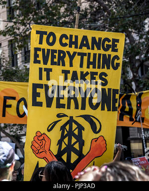 San Francisco, California, USA. 8th September, 2018. Thousands gather in San Francisco in Rise for Climate rally and march in advance of the Global Climate Action Summit to be held there September 12 to 14. A sign held above the crowd reads, 'To change everything it takes everyone' with fists in front of an oil tower.  Shelly Rivoli/Alamy Live News - Stock Photo
