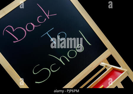 Text back to school written in various colors on blackboard. Isolated over black background. - Stock Photo
