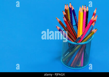 Colored pencils in a pencil case on blue background with copy space. - Stock Photo