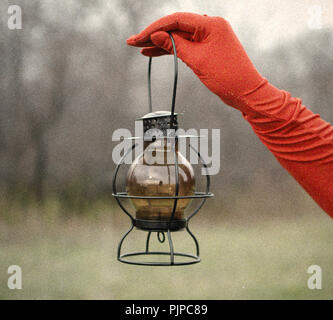 Lady in gloves holding an old lamp. Old, vintage style. - Stock Photo