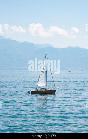 Small sail boat on Lake Leman (Geneva Lake) on beautiful sunny summer day with mountains and white clouds on the background - Stock Photo
