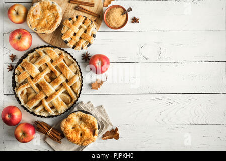 Homemade Apple Pies on white wooden background, top view. Classic autumn Thanksgiving dessert - organic apple pie. - Stock Photo