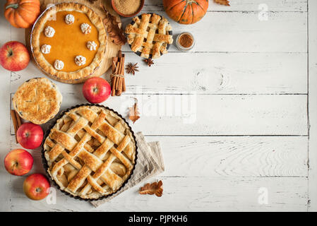 Thanksgiving pumpkin and apple various pies on white, top view, copy space. Fall traditional homemade apple and pumpkin pie for autumn holiday. - Stock Photo