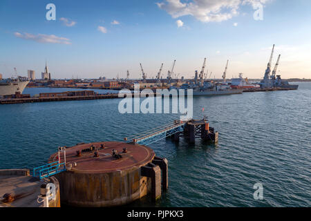 Portsmouth, Solent, UK - May 14, 2016: Portsmouth docks and coastline with ships in the early evening - Stock Photo