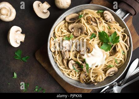 Mushroom Spaghetti Pasta and cream sauce on rustic background, top view. Homemade italian pasta with champignon mushroom in cooking pan. - Stock Photo