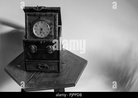 Antique clock sitting on an vintage table - Stock Photo