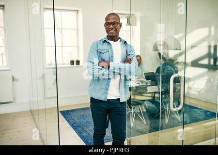 Young African businessman smiling confidently while standing with his arms crossed in an office with colleagues in the background - Stock Photo