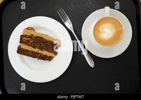 Overhead view of a cup of frothy milky coffee with heart shaped design, fork, chocolate walnut cake on black background in London UK  KATHY DEWITT - Stock Photo