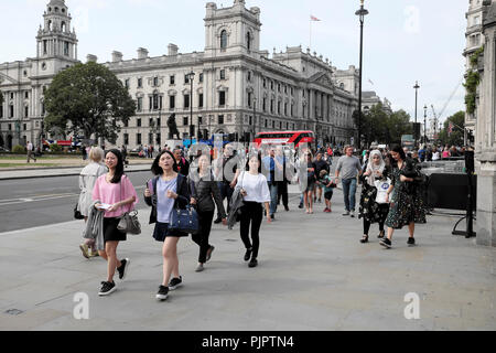 Tourists walking in the street outside the Houses of Parliament in Westminster, London SW1 England UK  KATHY DEWITT - Stock Photo
