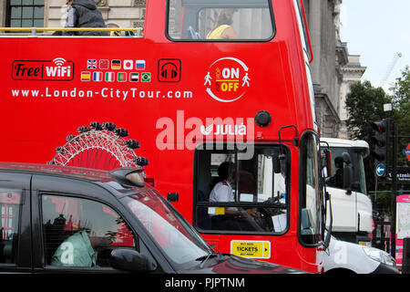 Red double-decker hop on - hop off City Tour tourist bus and driver stuck in Parliament Square traffic in City of Westminster London UK  KATHY DEWITT - Stock Photo