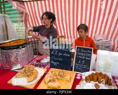 A Spanish woman stall holder at a UK farmer's market serving a portion of steaming hot Paella - Stock Photo