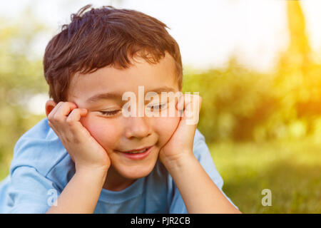 Child kid little boy day dreaming daydreaming thinking outdoor copyspace copy space outdoors outside nature - Stock Photo