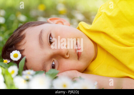 Child kid spring flower meadow flowers little boy day dreaming outdoor outdoors outside nature field - Stock Photo