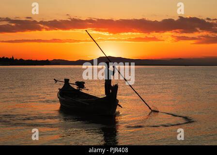 Silhouette of a youn fisherman on the Irrawaddy river at sunset, Nyaung U, Bagan, Myanmar (Burma). - Stock Photo