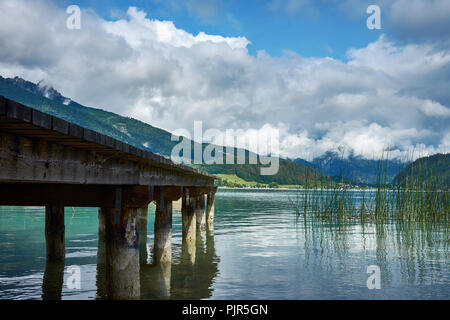View of the lake near St. Wolfgang with a wooden pier and Alps mountains background, under a blue sky with clouds on a sunny day - Stock Photo
