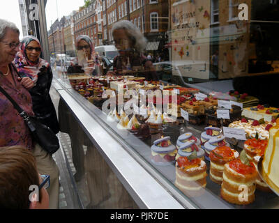 People look at cakes through a bakery shop window - Stock Photo