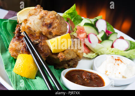 A plated meal of Chicken Karaage with red chili bean dip and Paprika yogurt served with a fresh mixed salad - Stock Photo