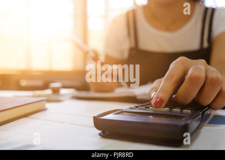 Close up of female Hand doing finances and calculate on desk about cost at home office. accountant or banker making calculations. Savings, finances an - Stock Photo