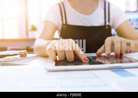 Cropped shot of Woman Touching stock market graph on a touch screen device in home. Trading on stock market concept. - Stock Photo