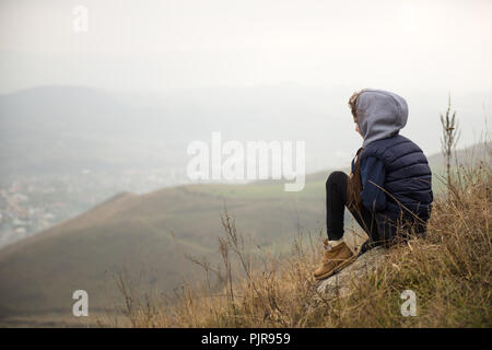 little girl in jacket with hood sitting on mountain during autumn hiking relaxing - Stock Photo