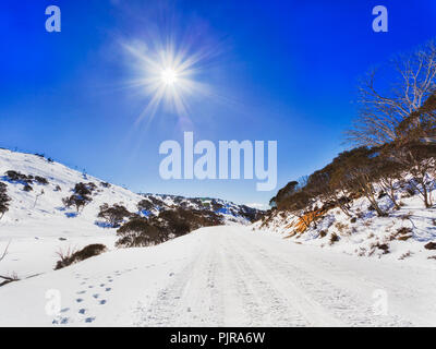 Snow covered road in SNowy mountains from Perisher valley to Charlotte pass suitable to snowmobiles only under blue sky with haze and sun surrounded b - Stock Photo