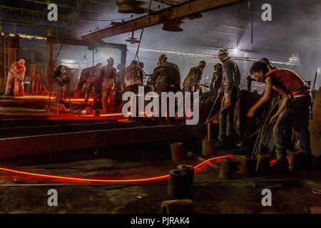 Indian industrial workers working hard in tough situation in foundry. - Stock Photo