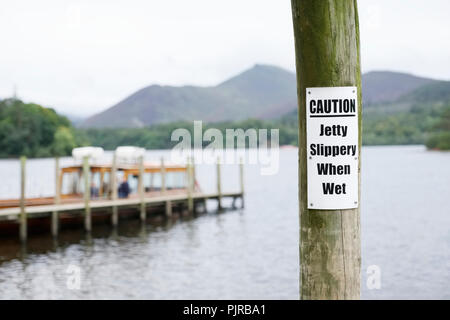 Jetty pier water safety sign slippery when wet at Derwentwater in the Lake District - Stock Photo