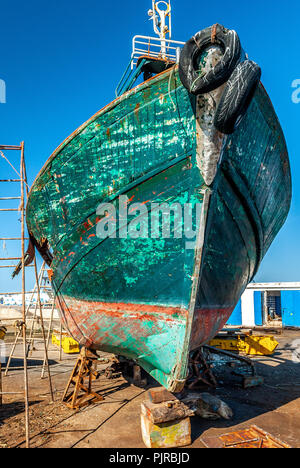 Repairs on the bow of a fishing boat in dry dock at the port of Essaouira in Morocco - Stock Photo