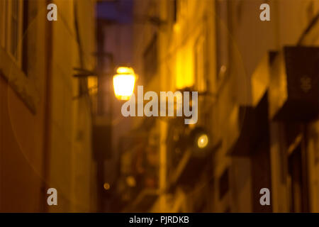 Blurred background. The lantern shines at night on a small street in the Alfama old district. Lisbon, Portugal. - Stock Photo