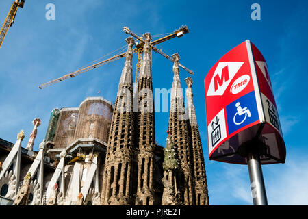 Sagrada Familia in Barcelona with metro sign in forefront and showing construction of new part - Stock Photo
