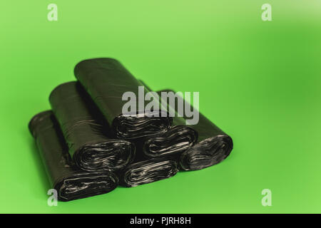 New black rolls of garbage bags against a green background. - Stock Photo