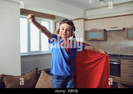 The boy in the costume of a superhero at the window - Stock Photo