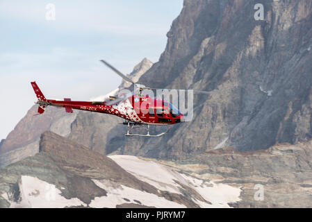 Swiss Helicopter in the Alps at Sunrise - Stock Photo