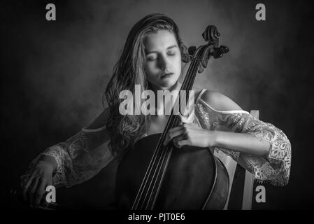 Studio portrait of a long haired, blonde woman playing the cello - Stock Photo