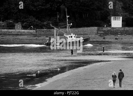 A small fishing boats pushes its way into Teignmouth Harbour through the fast moving tidal race. - Stock Photo