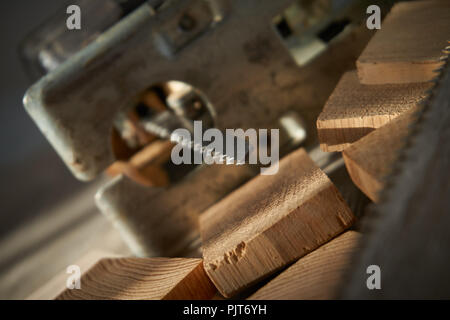 Close up electric jigsaw blade on top of wooden blocks - Stock Photo