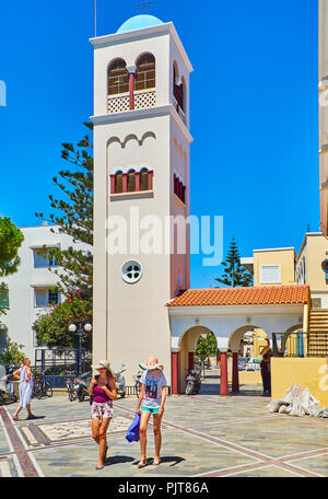 Kos, Greece - July 3, 2018.Tourists crossing the Agia Paraskevi square with the bell tower of the Church of Agia Paraskevi in background. South Aegean - Stock Photo