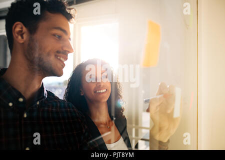Office colleagues discussing business ideas and plans on a transparent glass board. Business couple writing on sticky notes pasted on glass board in o - Stock Photo