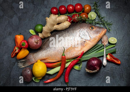 Fresh raw red snapper fish with spices, herbs and vegetables for cooking on dark background. Top view. - Stock Photo