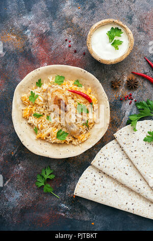 Chicken biryani with yogurt on a rustic background with spices, traditional spicy indian food. Pakistani fried rice.Top view,flat lay - Stock Photo