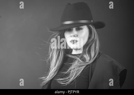 Studio portrait of a redhead woman in a coat and black hat looking at camera - Stock Photo