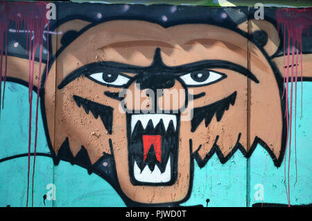 The old wall, painted in color graffiti drawing with aerosol paints. Picture of a terrible bear face - Stock Photo