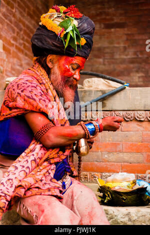 Pashupatinath, Nepal - July 17, 2018 : Holy Sadhu man with traditional painted face and colouful clothes is blessing people at Pashupatinath - Stock Photo