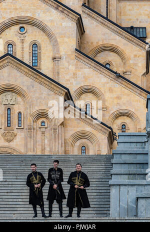 Tbilisi, Georgia / June 8, 2017 - Groomsmen stand in front of the Holy Trinity Cathedral of Tbilisi - Stock Photo