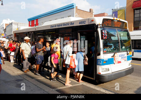New Yorkers queue to board a NYC Transit bus in Flushing, New York. - Stock Photo