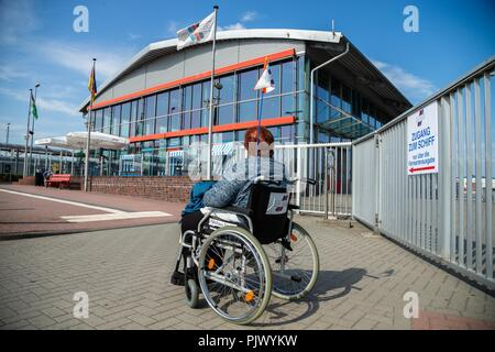 Emden, Germany. 05th Sep, 2018. A woman in a wheelchair is at the ferry station in front of a metal gate, on which a sign with the inscription 'Access to the ship - only via the ticket office' is attached. (on dpa 'severely disabled people fight for rights - also as ferry passengers' of 09.09.2018) Credit: Mohssen Assanimoghaddam/dpa/Alamy Live News - Stock Photo