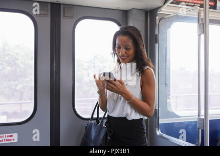 Businesswoman using cellphone in train - Stock Photo